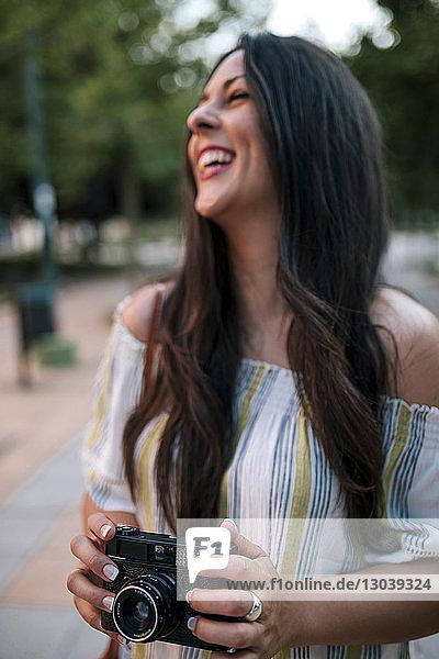 Fröhliche Frau  die eine Digitalkamera hält  während sie im Park steht