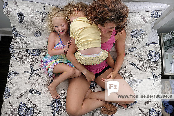 Hochwinkelaufnahme einer Mutter mit Töchtern  die zu Hause auf dem Bett sitzen