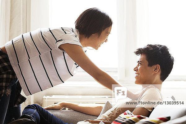 Seitenansicht einer glücklichen Frau  die sich an einen zu Hause sitzenden Mann lehnt