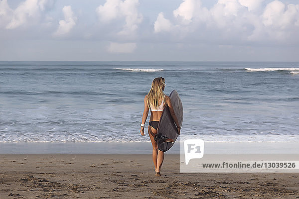Full length of woman carrying surfboard while walking towards sea at beach