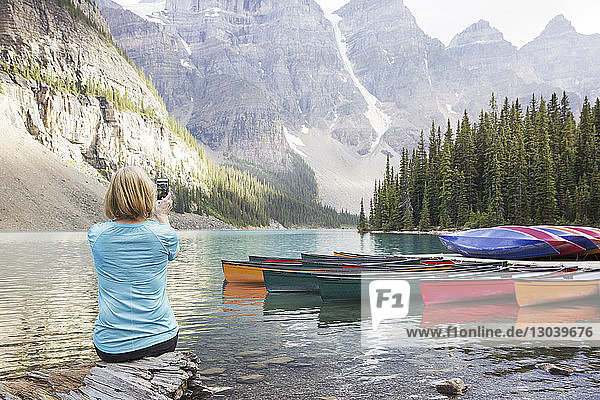 Rückansicht einer Frau  die mit einem Mobiltelefon fotografiert  während sie am Seeufer im Banff-Nationalpark sitzt