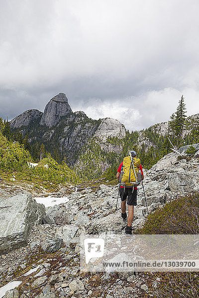 Rear view of hiker with backpack walking against mountains