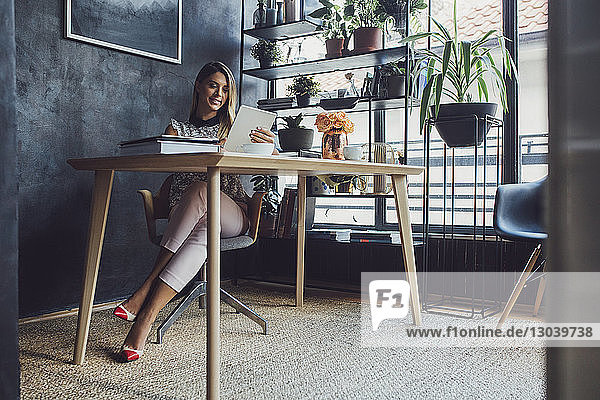 Smiling businesswoman working on tablet computer while sitting at table in home office