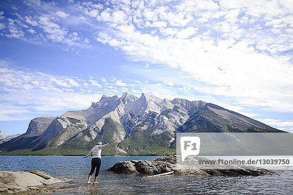 Wanderin in voller Länge beim Balancieren auf Baumstämmen gegen Berge im Banff-Nationalpark