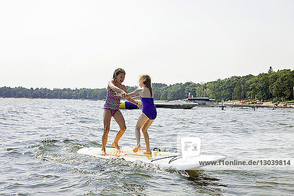 Full length of cheerful sisters standing on paddleboard in lake against clear sky during sunny day