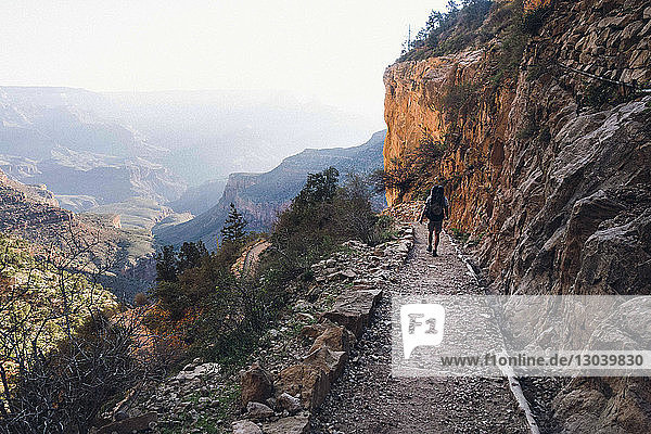 Rear view of man walking on footpath by mountain at grand canyon