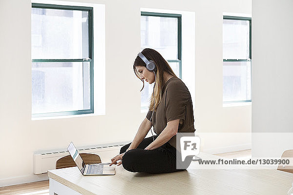 Side view of businesswoman listening music through laptop while sitting on desk in creative office