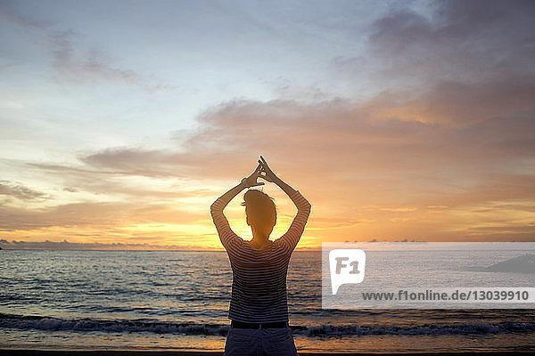 Rückansicht einer Frau mit erhobenen Armen  die bei Sonnenuntergang am Strand steht