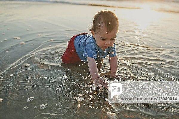High angle view of boy playing in water at beach during sunset