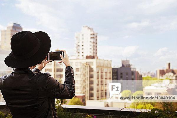 Rückansicht einer Frau  die Gebäude mit einem Smartphone von der Terrasse aus fotografiert