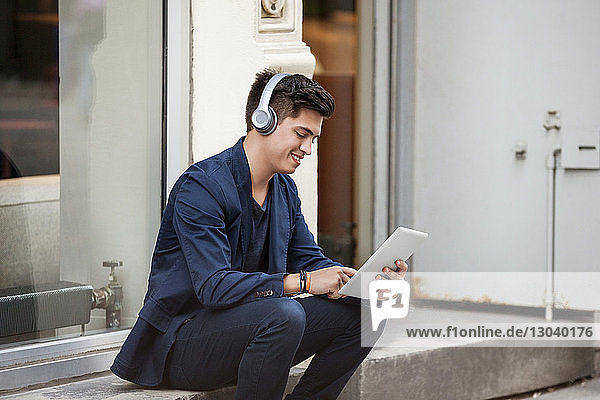 Glücklicher Geschäftsmann mit Tablet-Computer  der vor dem Gebäude sitzt Glücklicher Geschäftsmann mit Tablet-Computer, der vor dem Gebäude sitzt