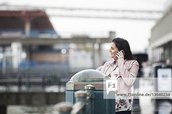 Lächelnde Frau spricht am Handy  während sie in der Stadt am Geländer steht