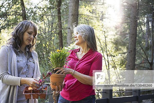 Mutter und Tochter bei der Gartenarbeit auf dem Balkon stehend