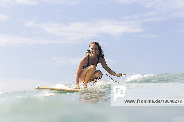 Portrait of smiling woman surfing on sea against sky