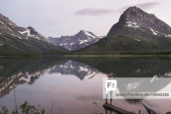 Rear view of hiker looking at Mt. Grinnell while standing on wood by Swiftcurrent Lake