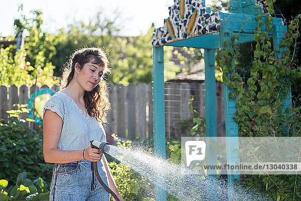 Frau gießt Pflanzen im Garten mit einem Schlauch