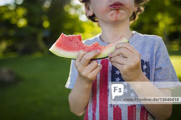 Mitschnitt eines Jungen  der im Hinterhof stehend eine Wassermelone isst