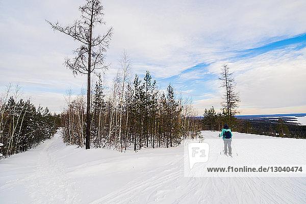 Rückansicht eines Skifahrers beim Skifahren auf schneebedecktem Feld vor bewölktem Himmel