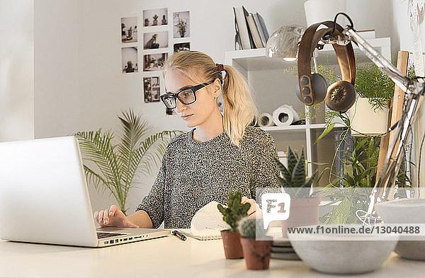 Geschäftsfrau benutzt Laptop  während sie am Schreibtisch bei Zimmerpflanzen im Kreativbüro sitzt