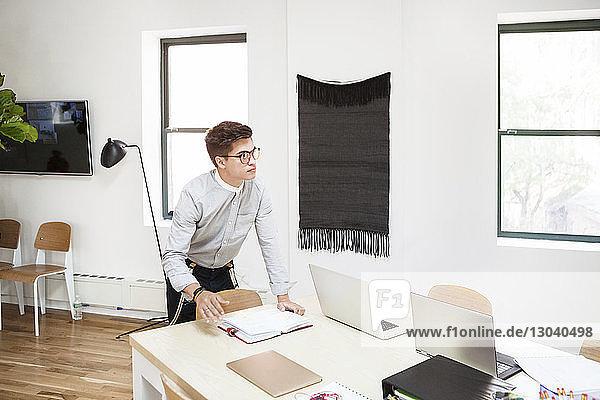 Nachdenklicher Geschäftsmann steht am Schreibtisch im Kreativbüro Nachdenklicher Geschäftsmann steht am Schreibtisch im Kreativbüro