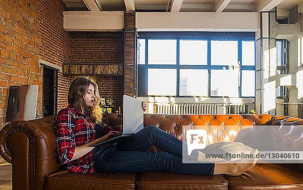 Junge Frau in voller Länge mit Laptop-Computer  während sie zu Hause auf einem Ledersofa sitzt