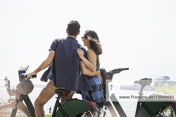 Rear view of affectionate couple with bicycles against clear sky