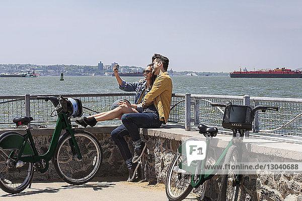 Paar  das sich beim Sitzen am Beobachtungspunkt vor klarem Himmel Selbsthilfe nimmt
