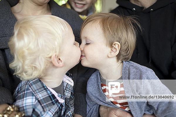 Brüder  die sich küssen  während sie bei der Familie zu Hause sitzen