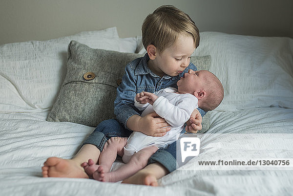 Junge sitzt mit neugeborenem Bruder zu Hause im Bett