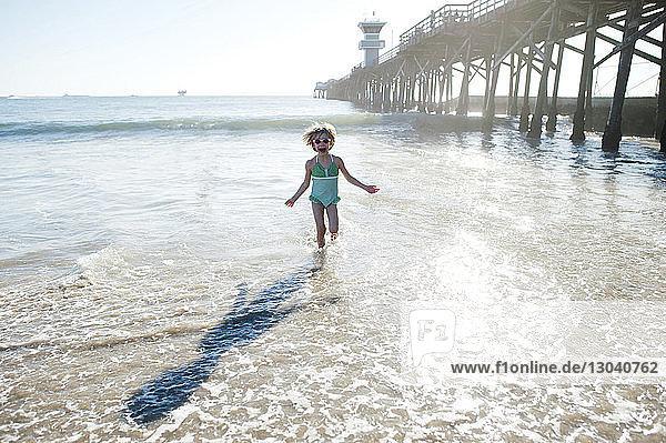 Girl running on shore at seal beach against sky