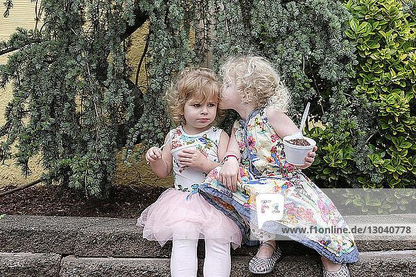 Schwester küsst Mädchen  während sie im Park Essen hält