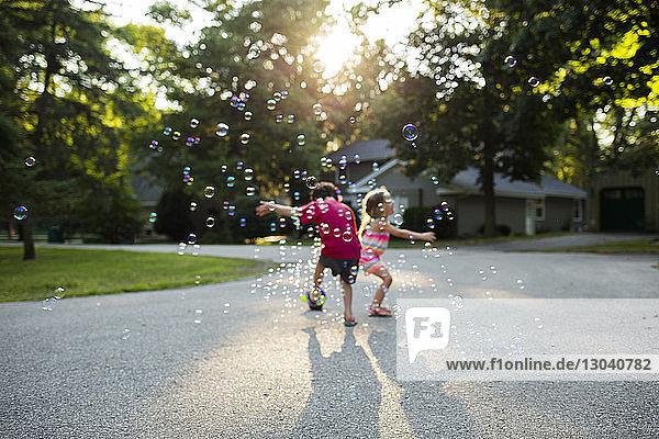 Geschwister spielen mit Seifenblasen auf dem Fußweg