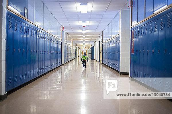 Rückansicht eines auf dem Schulkorridor laufenden Jungen