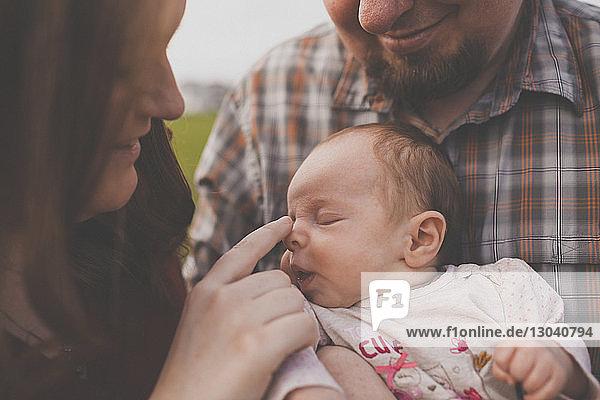 Nahaufnahme von Eltern  die mit ihrer niedlichen Tochter im Park spielen