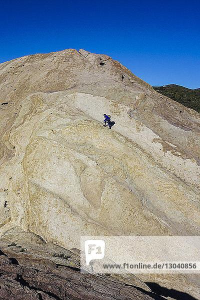 Mitteldistanzansicht einer Wanderin  die auf einem Berg gegen den Himmel läuft