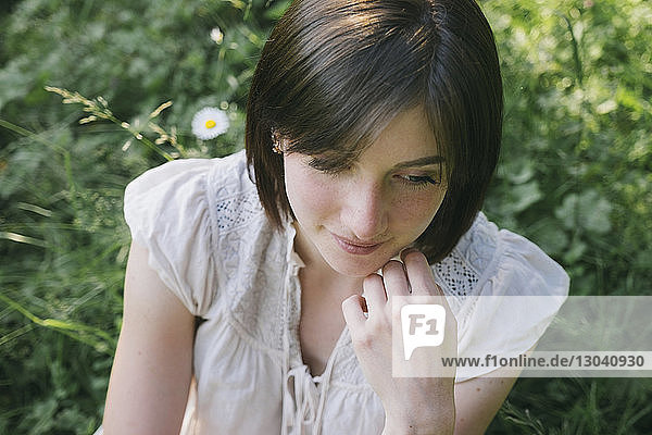 High angle view of thoughtful young woman looking away in forest