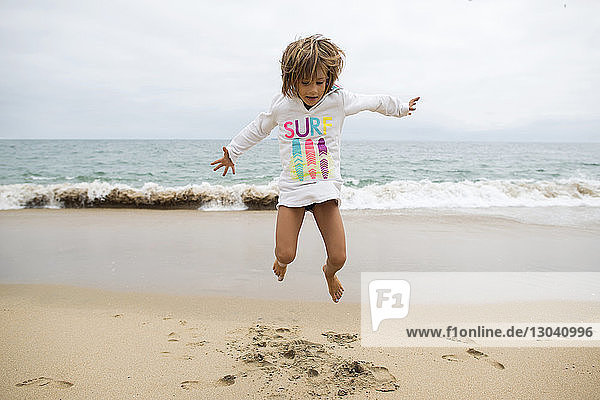 Playful girl jumping at Seal Beach against clear sky
