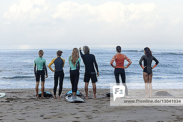 Full length rear view of friends with surfboards standing on shore at beach against sky