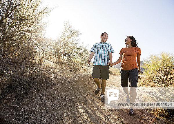 Glückliches Paar geht auf Feldweg gegen klaren Himmel