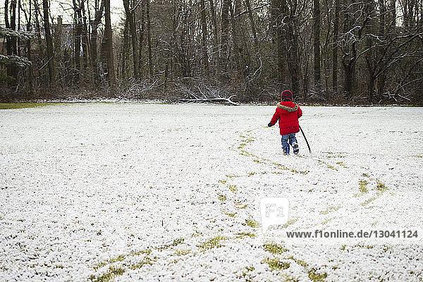 Rückansicht eines Jungen  der einen Stock hält  während er auf einem verschneiten Feld geht