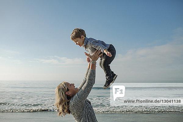 Lesbische Mutter wirft Sohn in die Luft  während sie am Strand gegen Meer und Himmel spielt