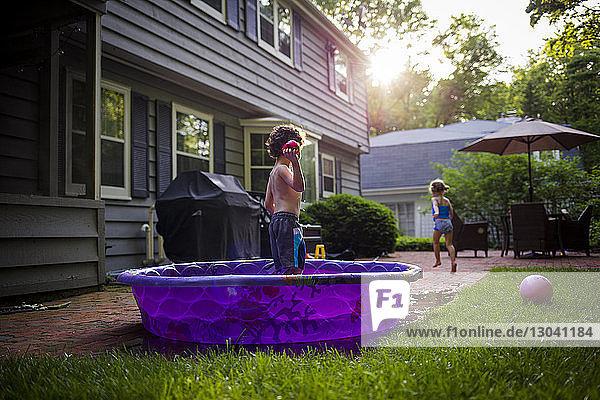 Mädchen läuft  während der Bruder im Planschbecken im Hinterhof steht