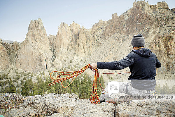 Rückansicht eines Felskletterers  der ein Seil wirft  während er am Berg sitzt