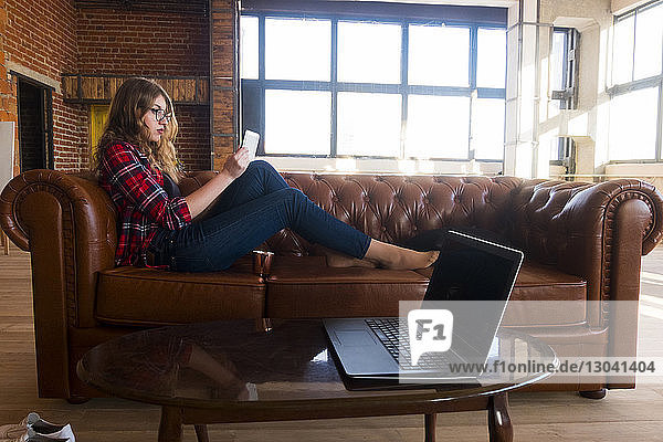 Side view of young woman using tablet computer while sitting on leather sofa at home