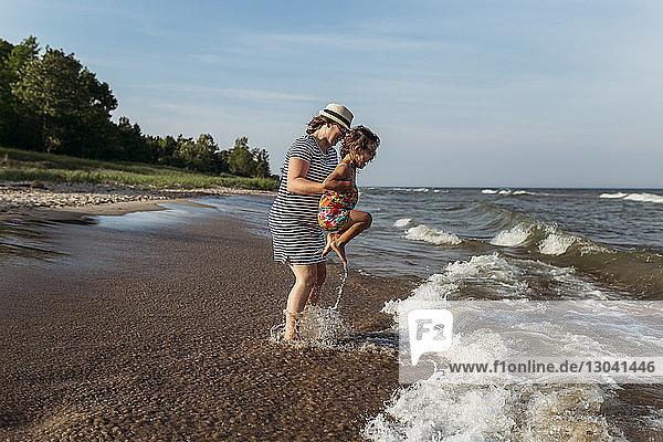 Mutter und Tochter spielen in Wellen am Strand gegen den Himmel