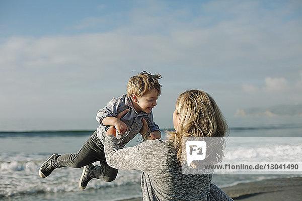 Lesbische Mutter hebt Sohn beim Spielen am Strand gegen Meer und Himmel