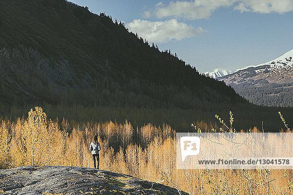 Rückansicht einer Wanderin  die auf einem Bergfelsen stehend die Aussicht betrachtet