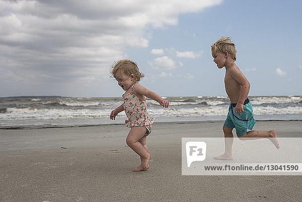 Seitenansicht von verspielten Geschwistern  die am Strand gegen bewölkten Himmel rennen