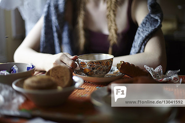 Midsection of woman holding tea cup while sitting at dining table