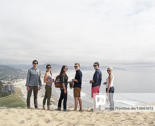 Porträt von Freunden,  die auf Sand am Strand gegen den Himmel stehen